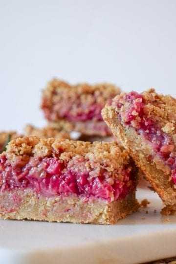Strawberry crumb bars on a white cutting board