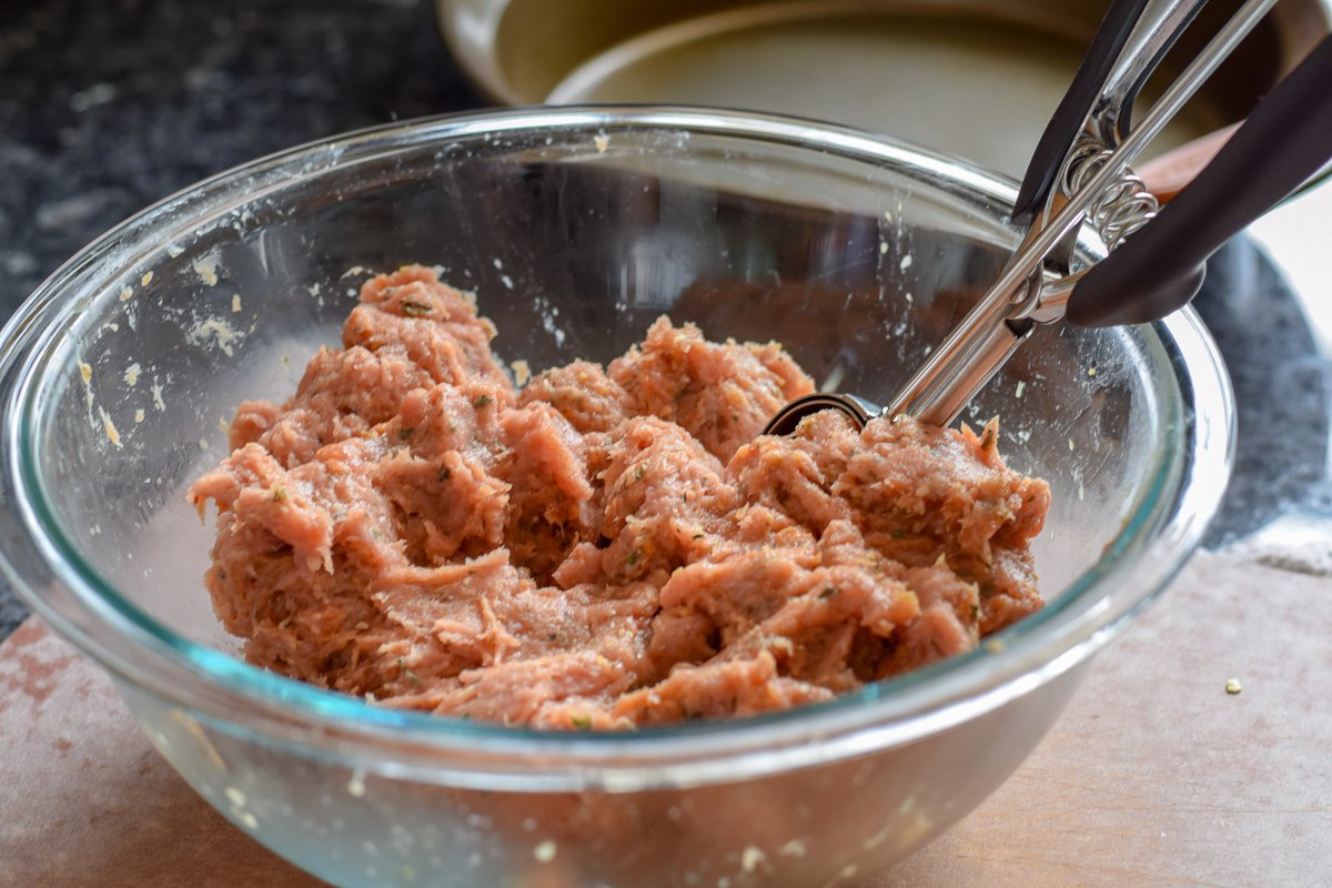 Raw ground turkey in a bowl with a scoop