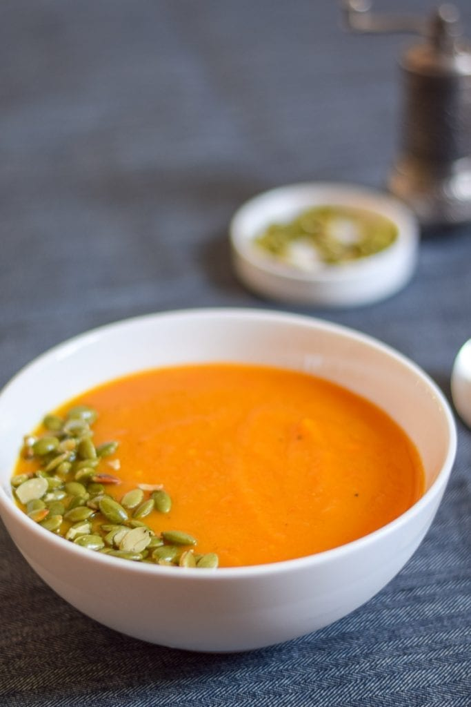 Squash soup in a white bowl with pepitas